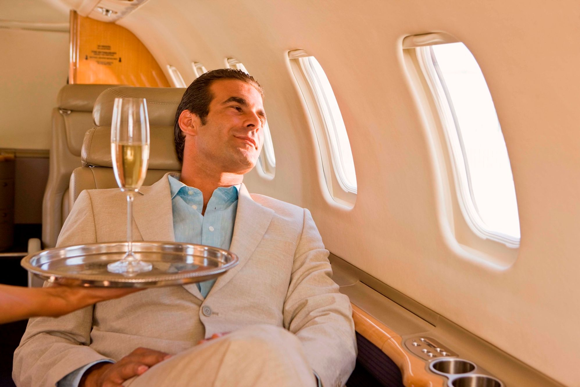 Man traveller offered champagne in first class - 10 things you should never do when flying