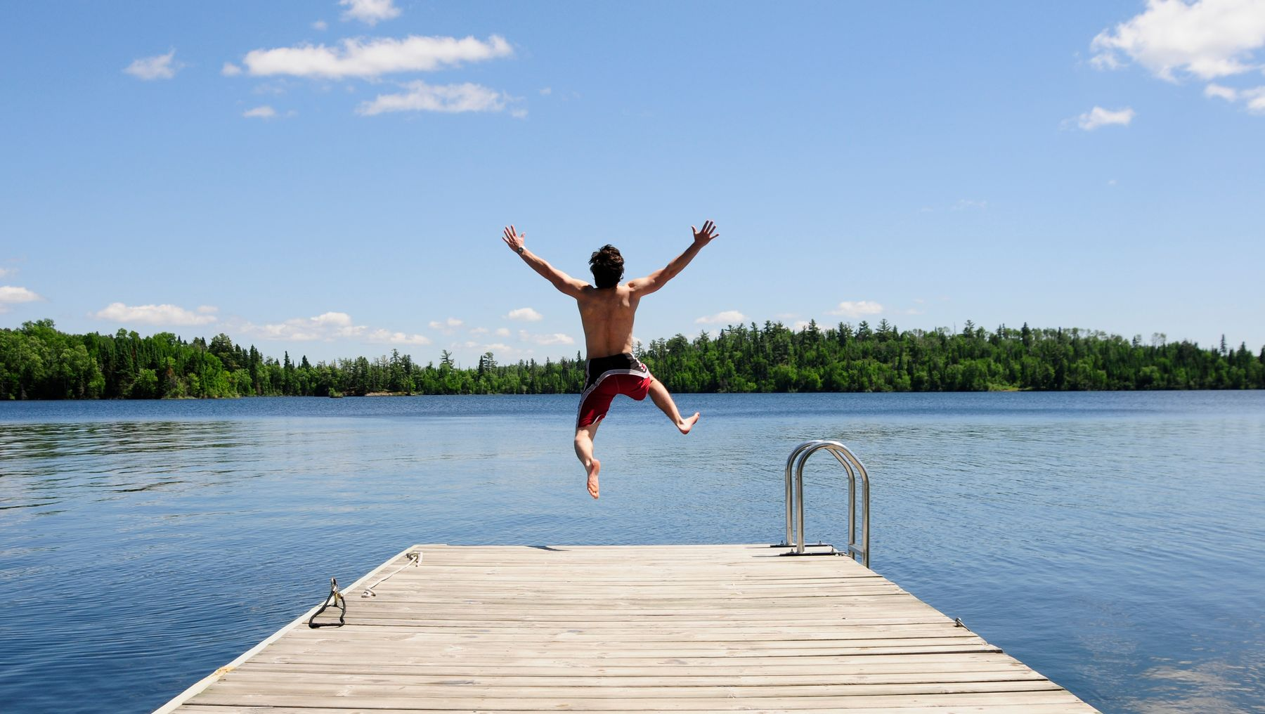 person jumping into a lake