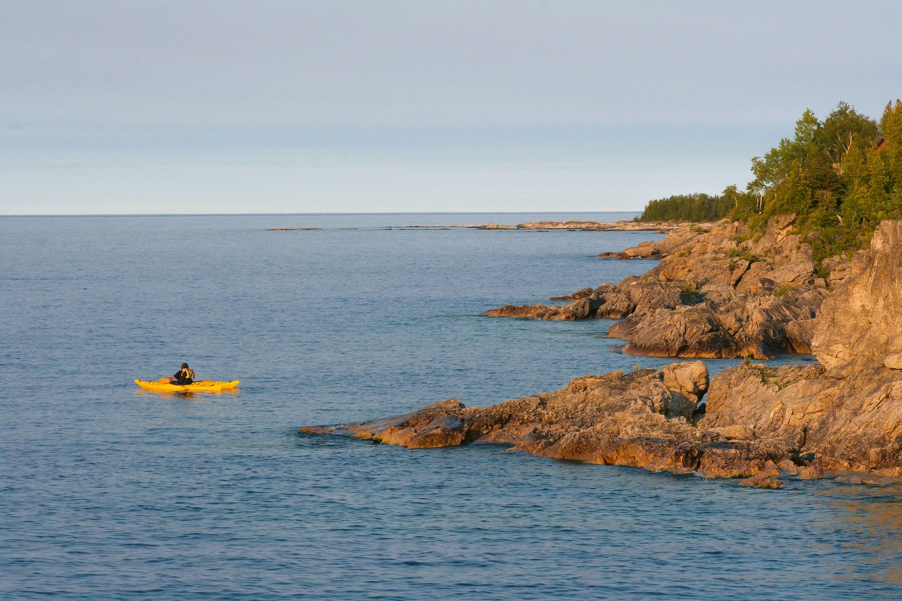 kayak in the water by the rocky shores of Georgian Bay, Ontario, around late afternoon