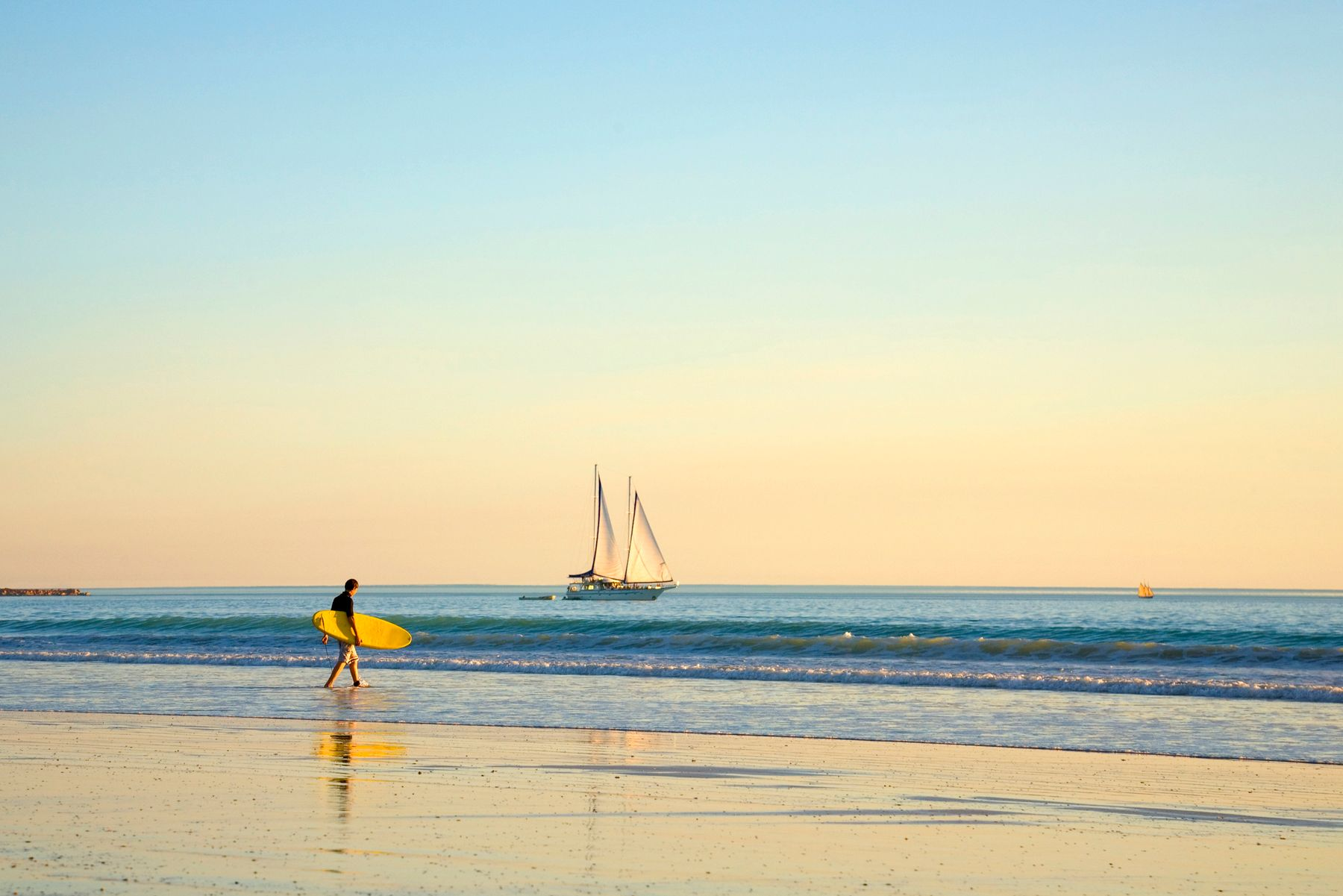 Man on beach with surfboard in Broome