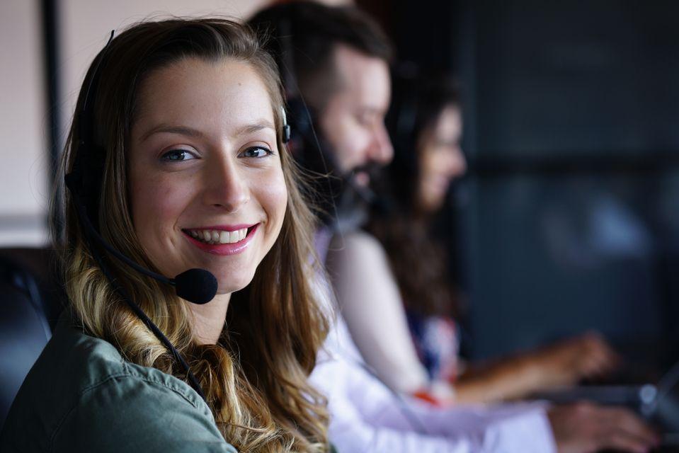 Χαμογελαστή υπάλληλος μιλάει στο τηλέφωνο