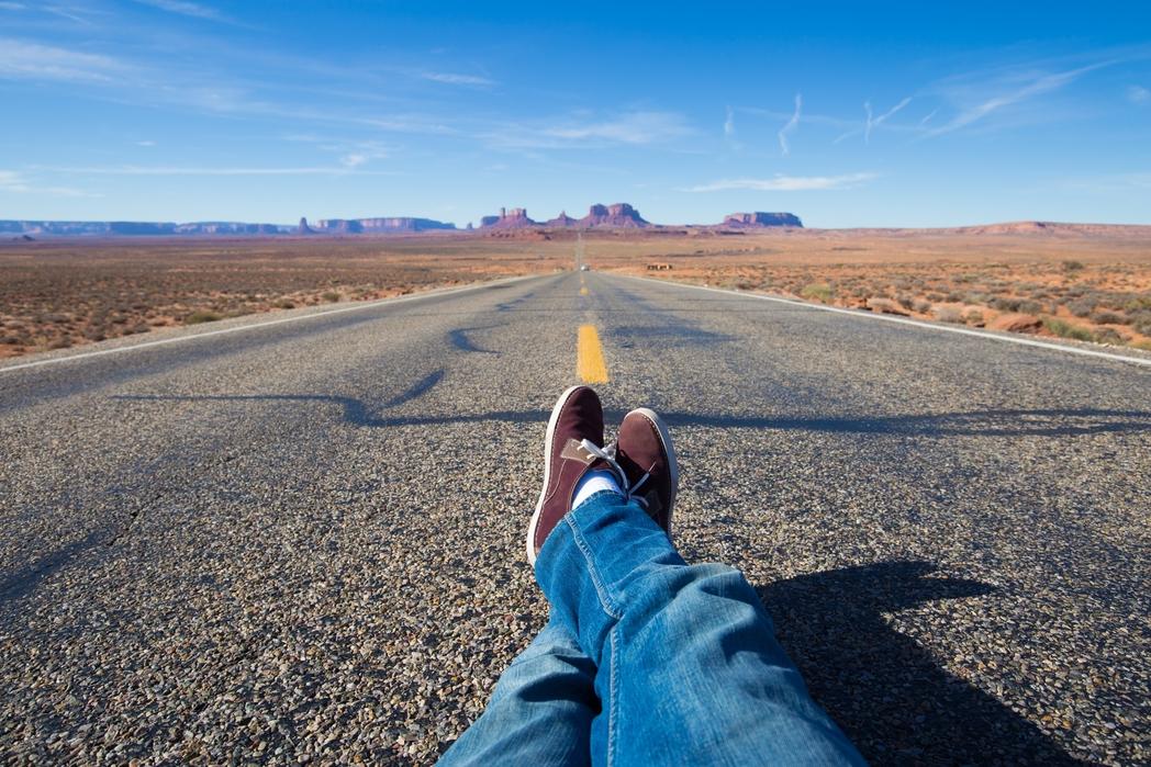 Ταξιδιώτης ξαπλώνει στη μέση του δρόμου με τη Monument Valley της Αριζόνα στο βάθος
