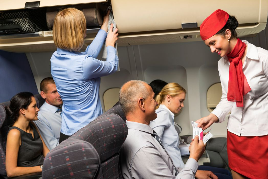 Cabin crew talking to a passenger on a plane