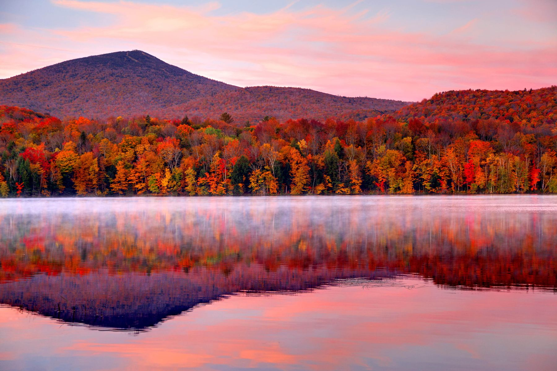 A lake reflects red, yellow, and orange fall trees. See the leaves change colors in one of these best destinations to travel to in October