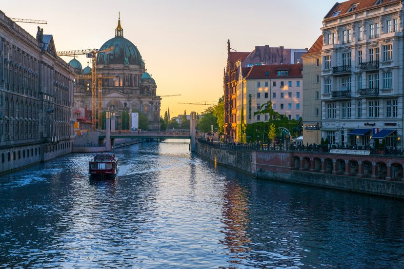 view of a boat along the canal in Berlin with the Berlin Cathedral in the background