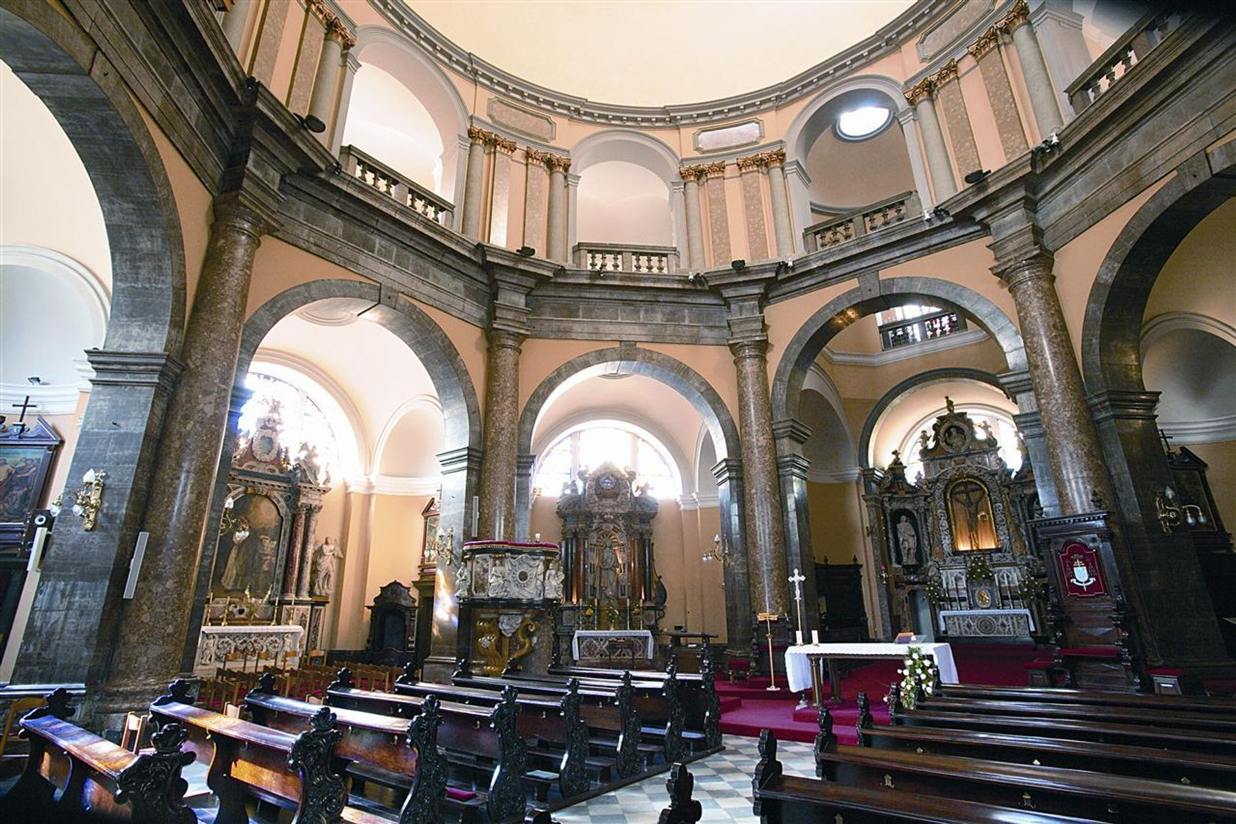 Photo shows the interior of Rijeka Cathedral in Croatia, showing the ornate interior design of marble arches and wooden pews, with a domed ceiling,