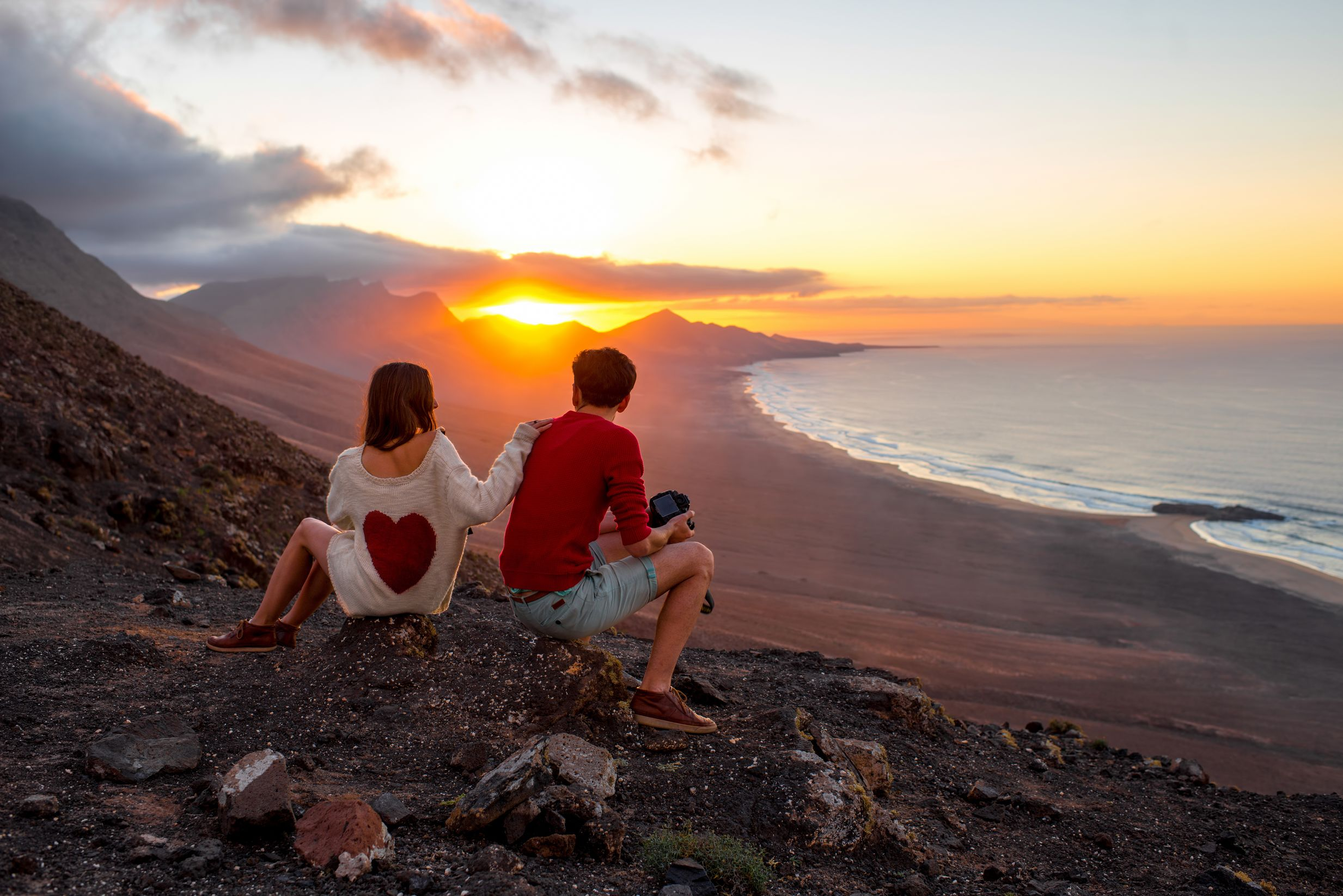 A couple look at the sunset from a volcano in Fuerteventura, Spain