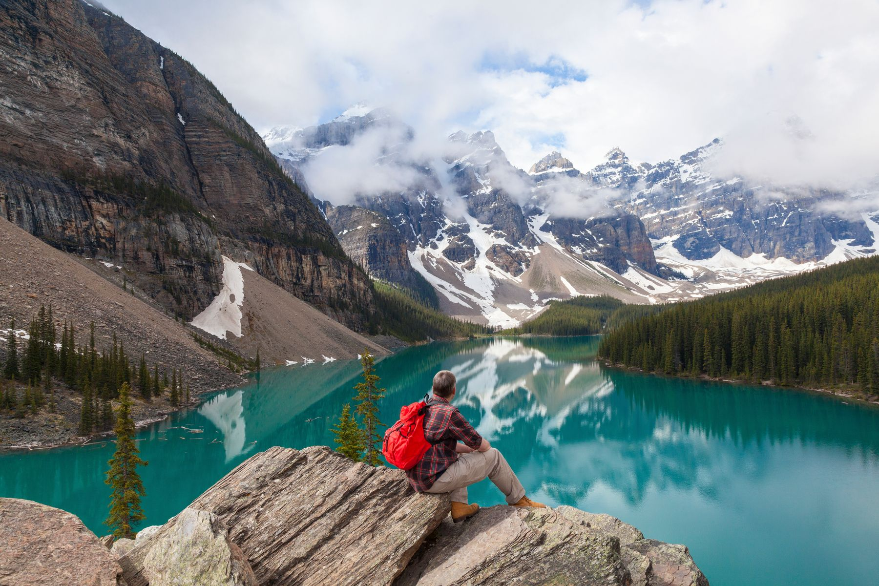 view from behind, a hiker sitting on a rock looking out at a glacial turquoise lake and the Canadian Rockies