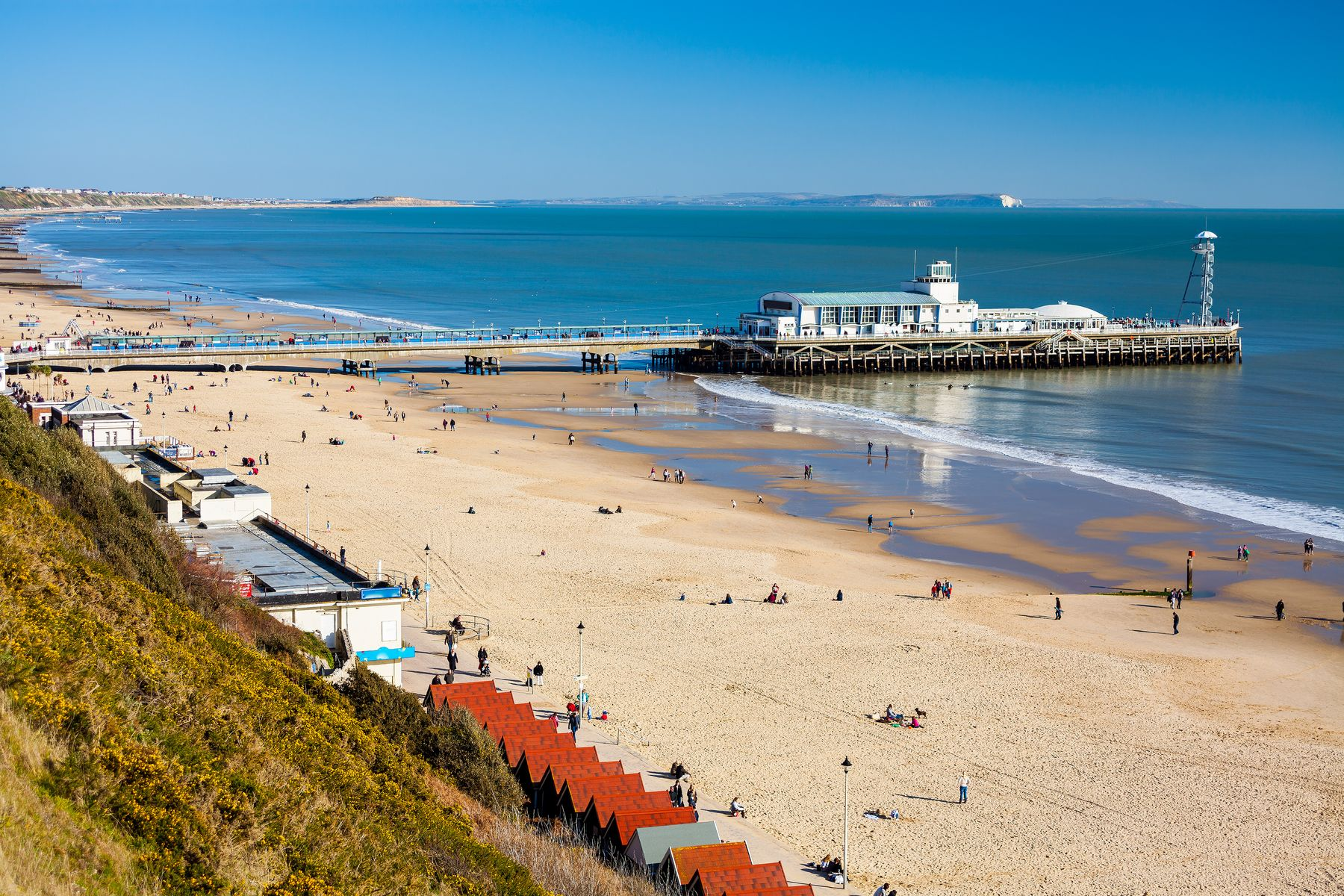 Picture shows Bournemouth Pier, the beach, and beach huts on a sunny day, with people having fun on the sand.