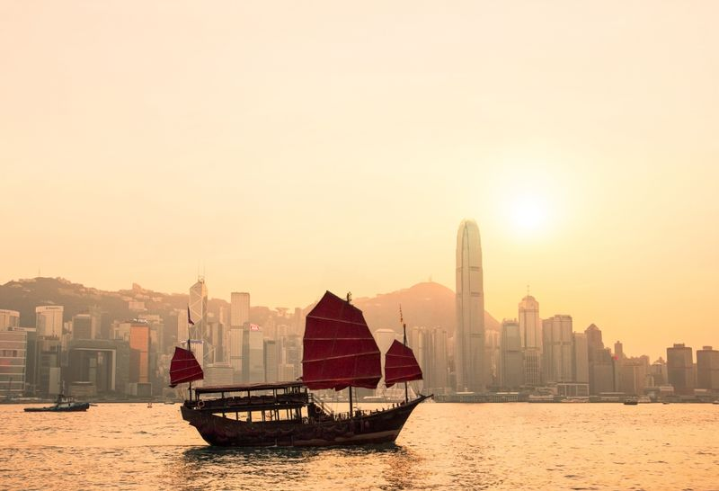 Hong Kong Harbour at sunset with a traditional sailing junk on the water