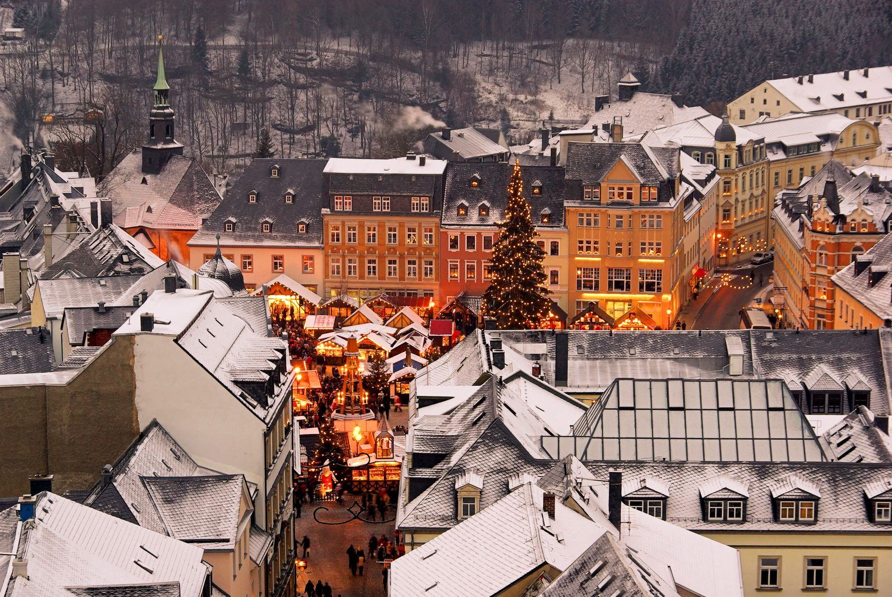 the snow top of buildings surround a street level market which glows red and gold with christmas magic