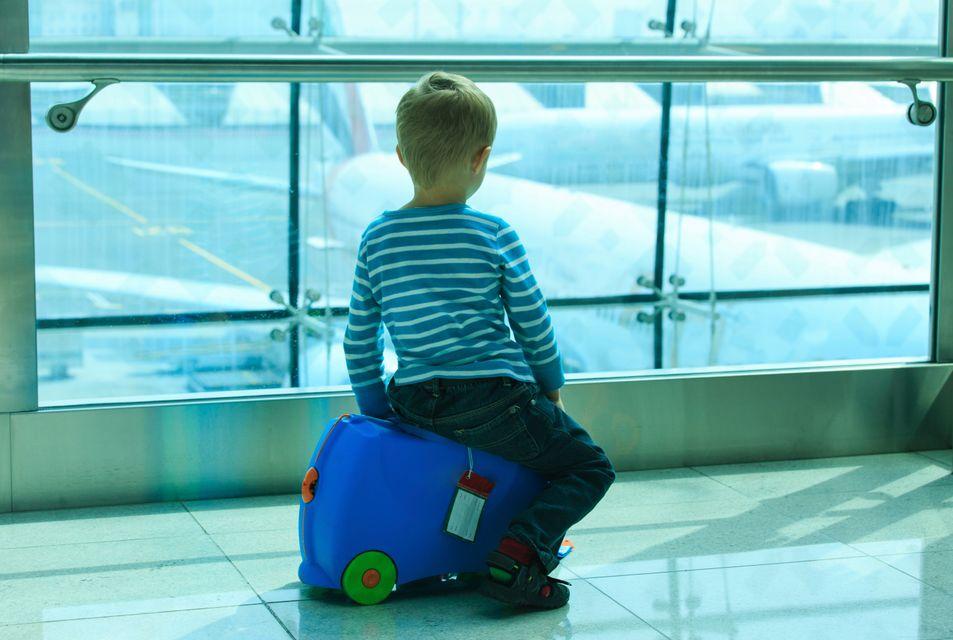 Μικρό παιδί παρακολουθεί τα αεροπλάνα μέσα από τον τερματικό σταθμό αεροδρομίου