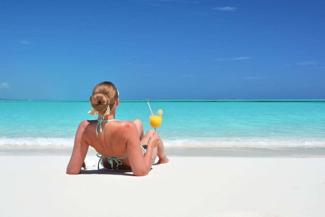 Γυναίκα πίνει κοκτέιλ στην άμμο στις Μπαχάμες - Πού να πάτε ταξίδι τον Δεκέμβριο