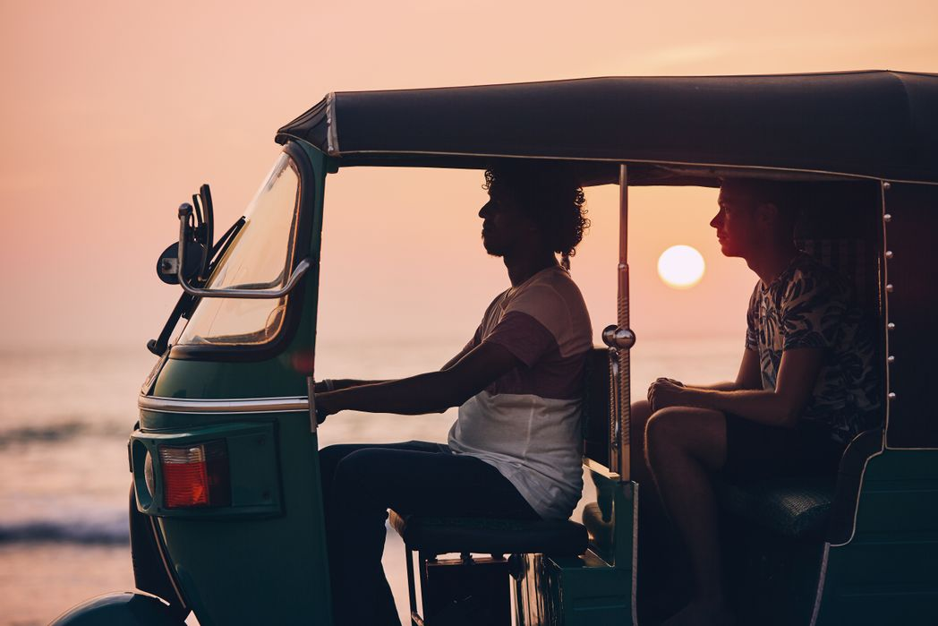 Driver and passenger are traveling by tuk tuk taxi against sea at sunset in Sri Lanka.