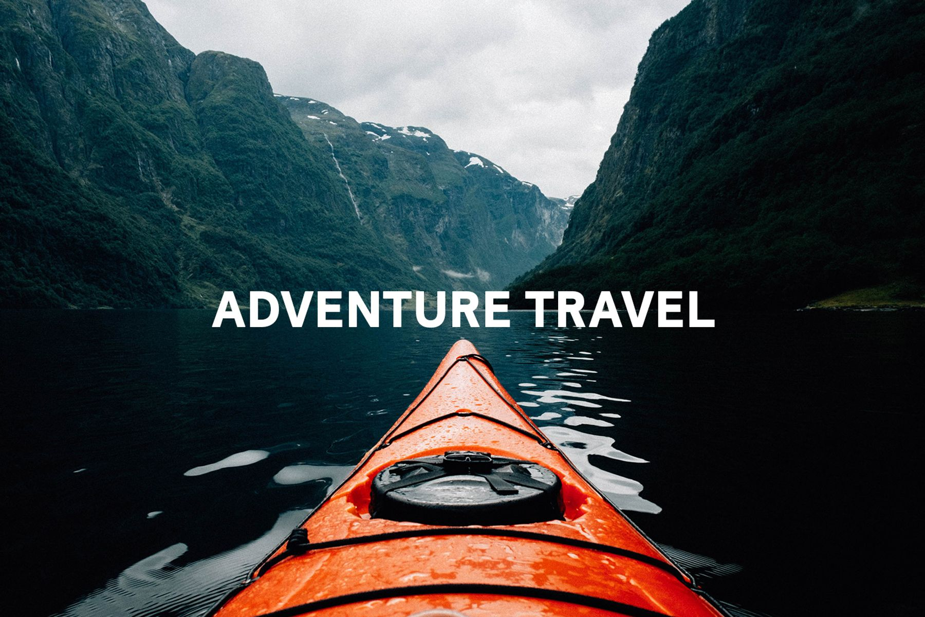 """Tip of red kayak on the water between two cliffs with the words """"adventure travel"""" in the middle of the photo"""
