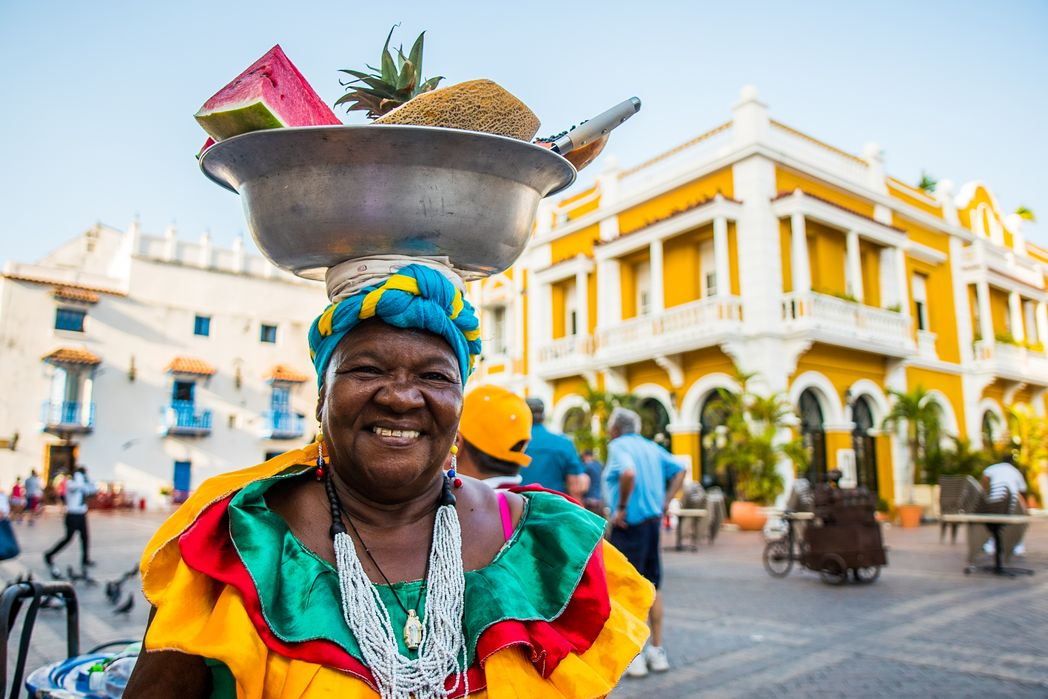 Palenquera with basket of fruit on head, Cartagena - reasons to visit Colombia