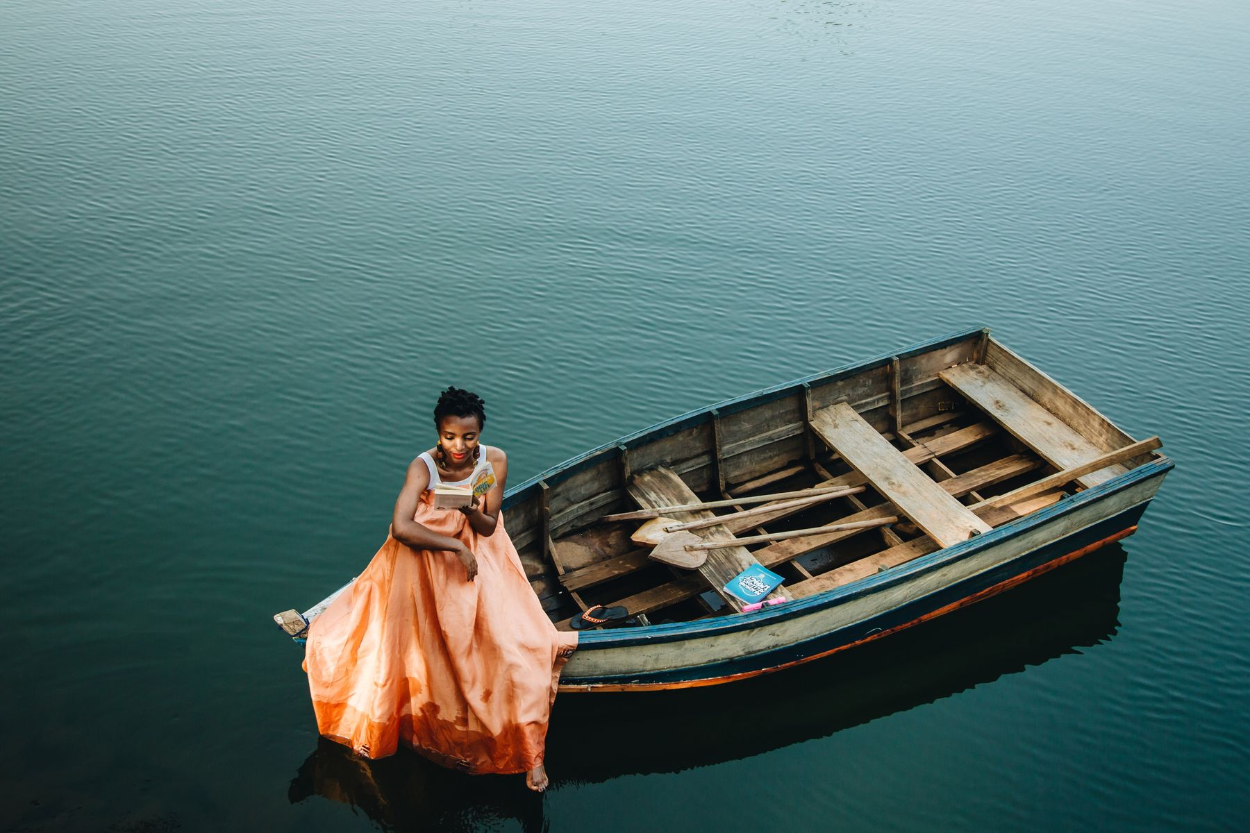 woman sitting at the tip of a wooden boat and reading in a meditative position