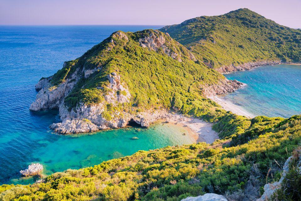 Narrow strip of beach among green topped hills at Pirates Bay, Corfu