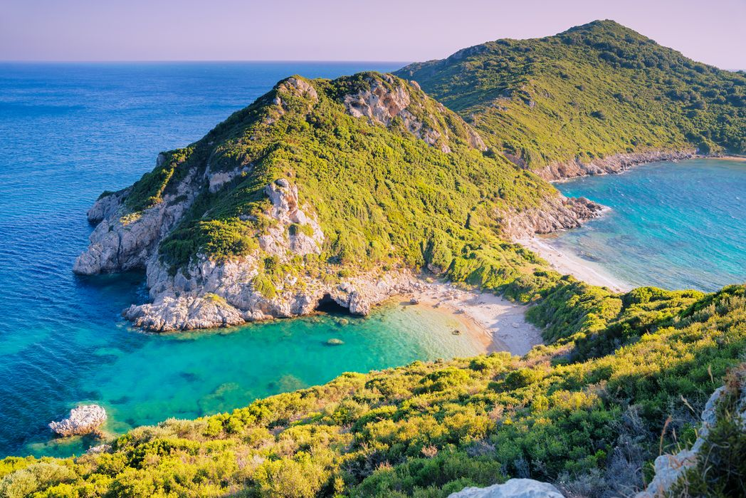 Narrow strip of beach among green topped hills at Pirates Bay, Corfu