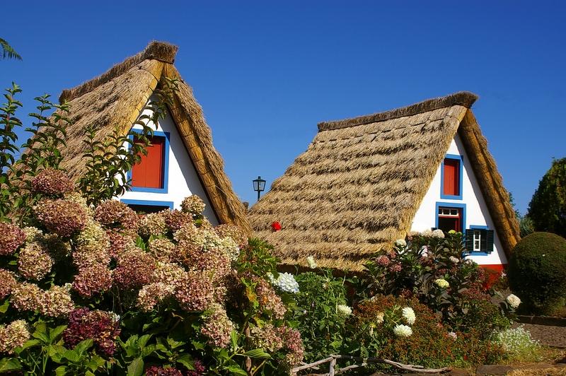 Треугольные домики Сантаны на Мадейре с соломенными крышами до земли
