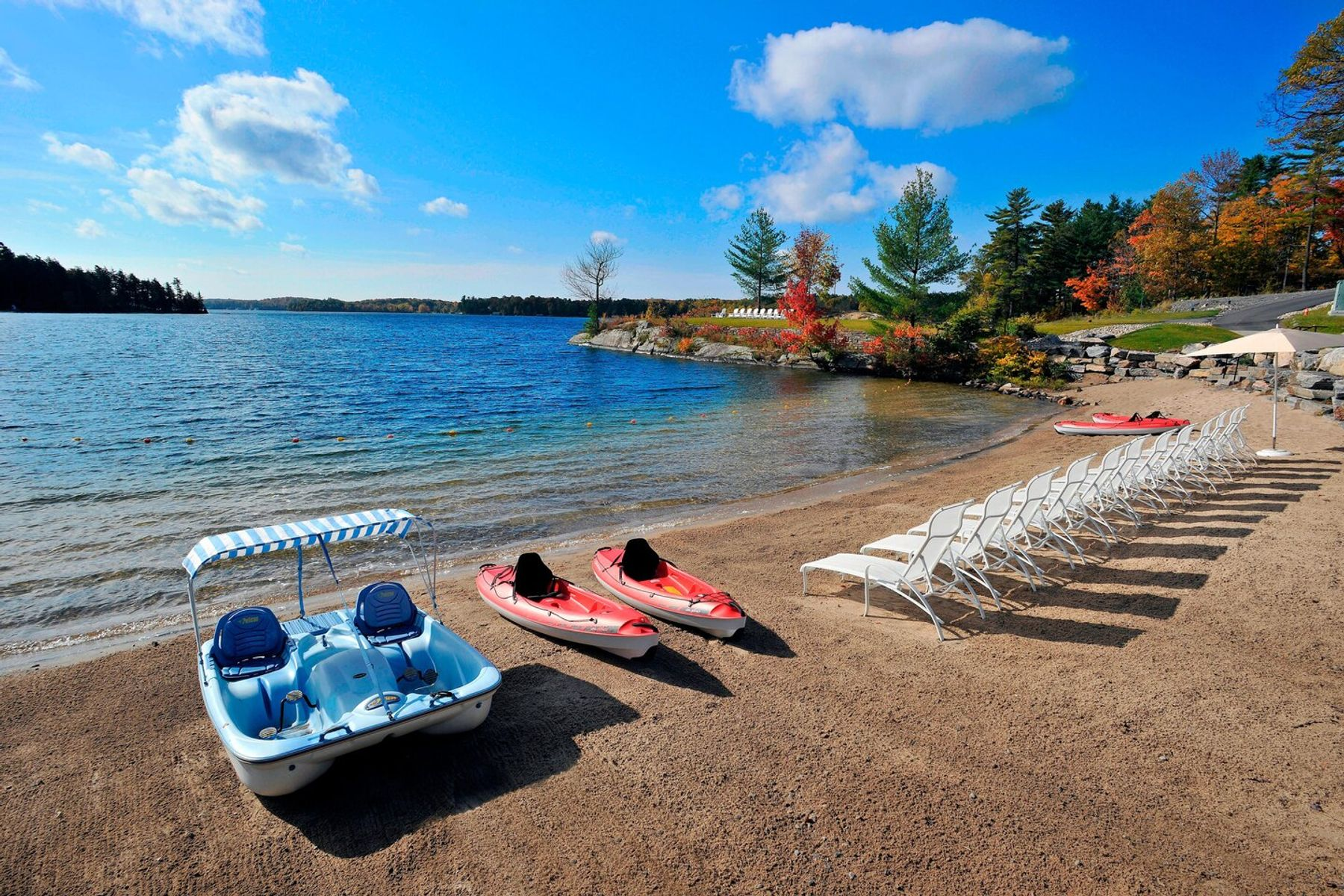 Best beach hotel views at J W Muskoka with kayaks, paddle boards and lounging chairs by the water