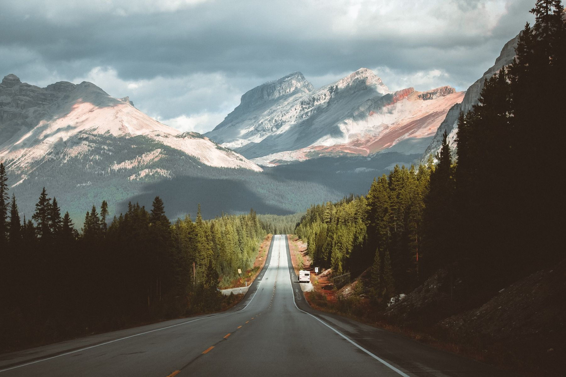 Open road through forests, heading to mountains, in Alberta Canada