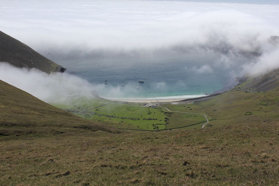 View from a hillside on the island of Hirta, looking down towards a beach with a few small boats in the cloudy bay.