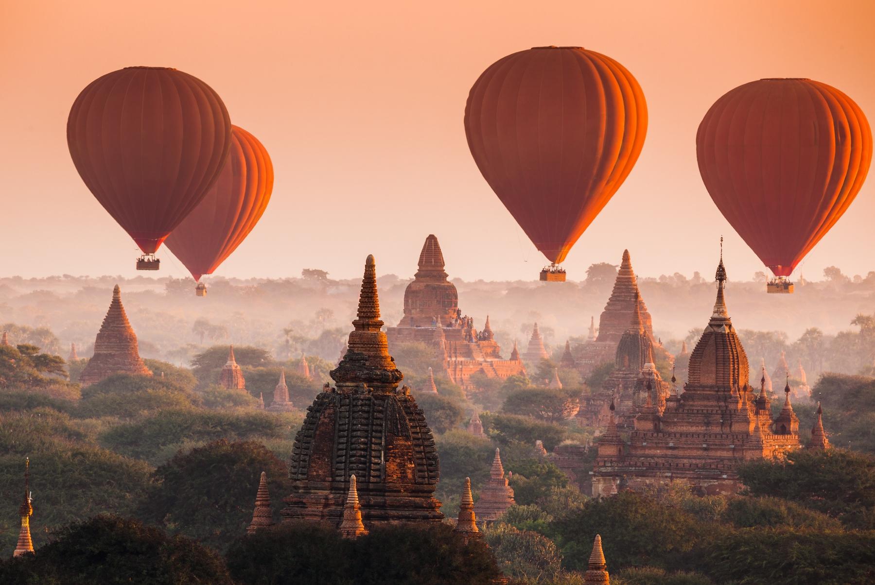 Воздушные шары летят над тысячей пагод Багана, окутанных золотой дымкой