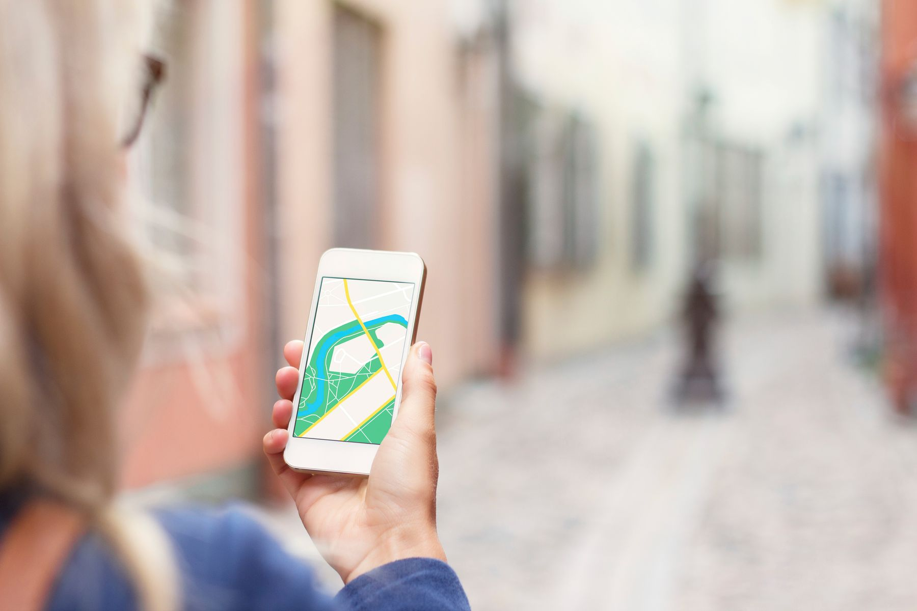 person navigating a street with an app on their smartphone