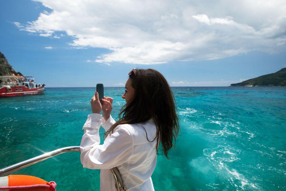 Τουρίστες φωτογραφίζουν τη θέα του νησιού από το καραβάκι - μία απ' τις must δραστηριότητες σε ένα ταξίδι στη Ζάκυνθο