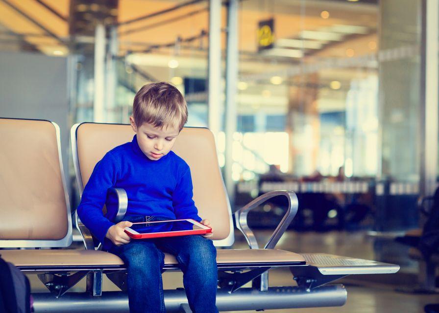 Μικρό παιδί σε αίθουσα αναμονής αεροδρομίου κοιτάζει το tablet του