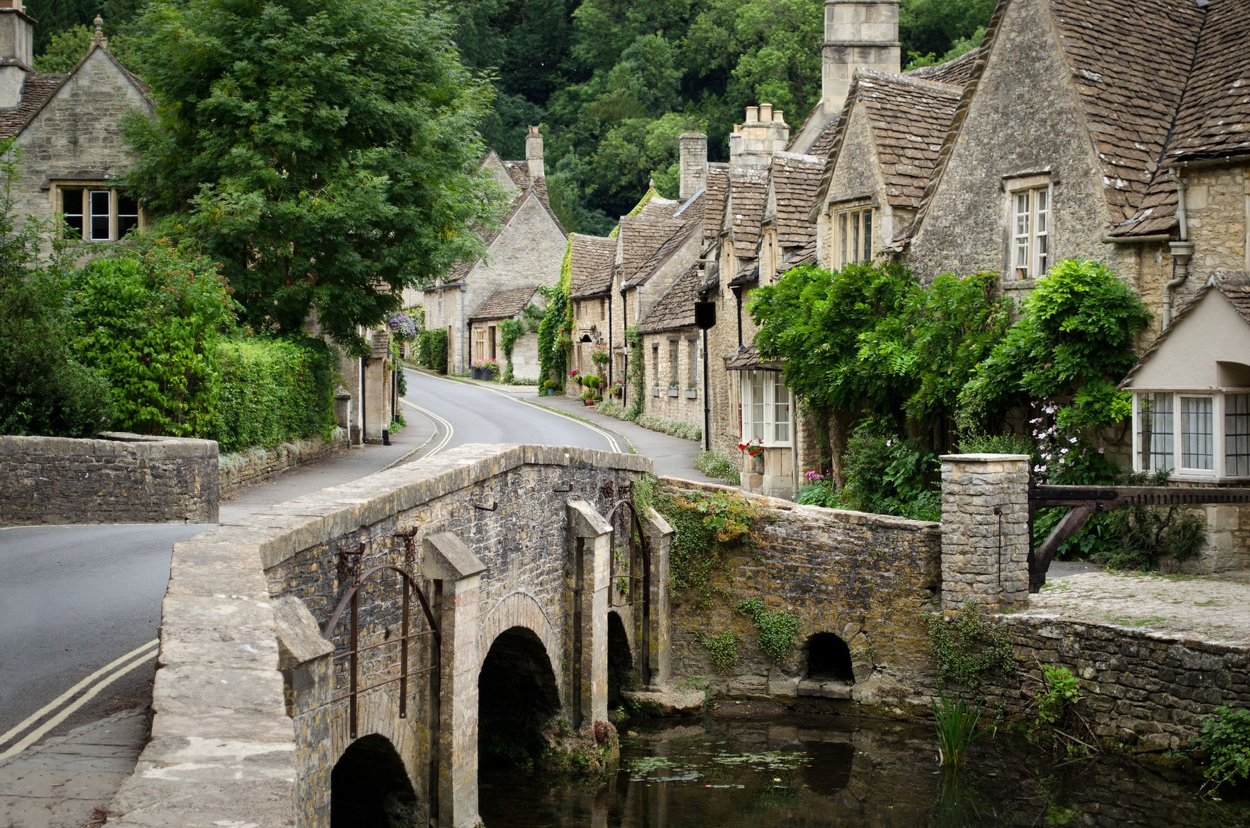 Pretty cottages line a street leading up to a stone bridge over a river in Castle Combe, a Cotswolds town perfect for spring holidays