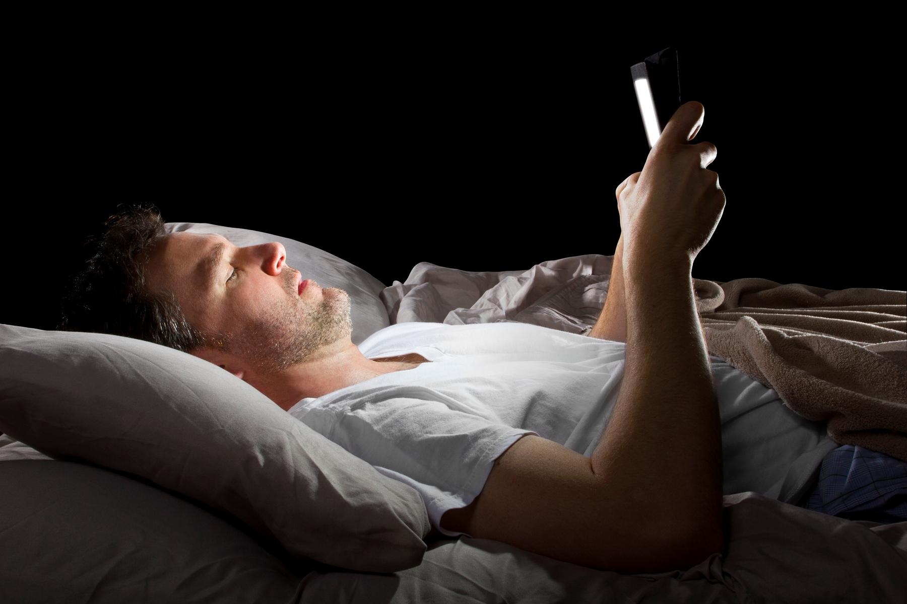 Homem deitado no escuro, com o celular em mãos, buscando passagens aéreas de madrugada.