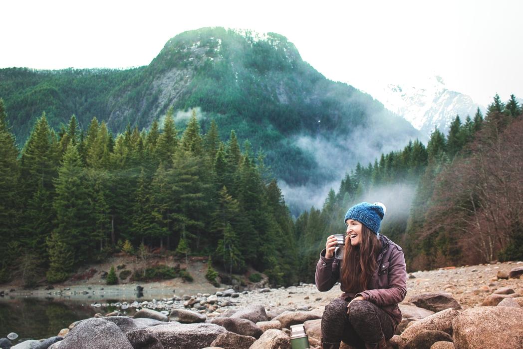 Ταξιδιώτρια κάνει στάση για ρόφημα στο δάσος - 20 συμβουλές και tips για πράσινα ταξίδια το 2020