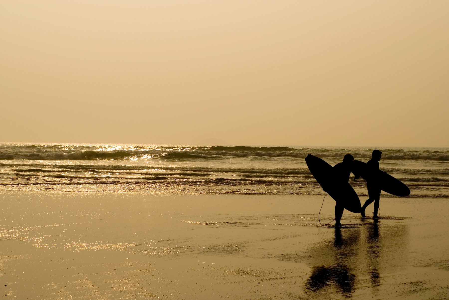 Surfers at sunset in Cornwall