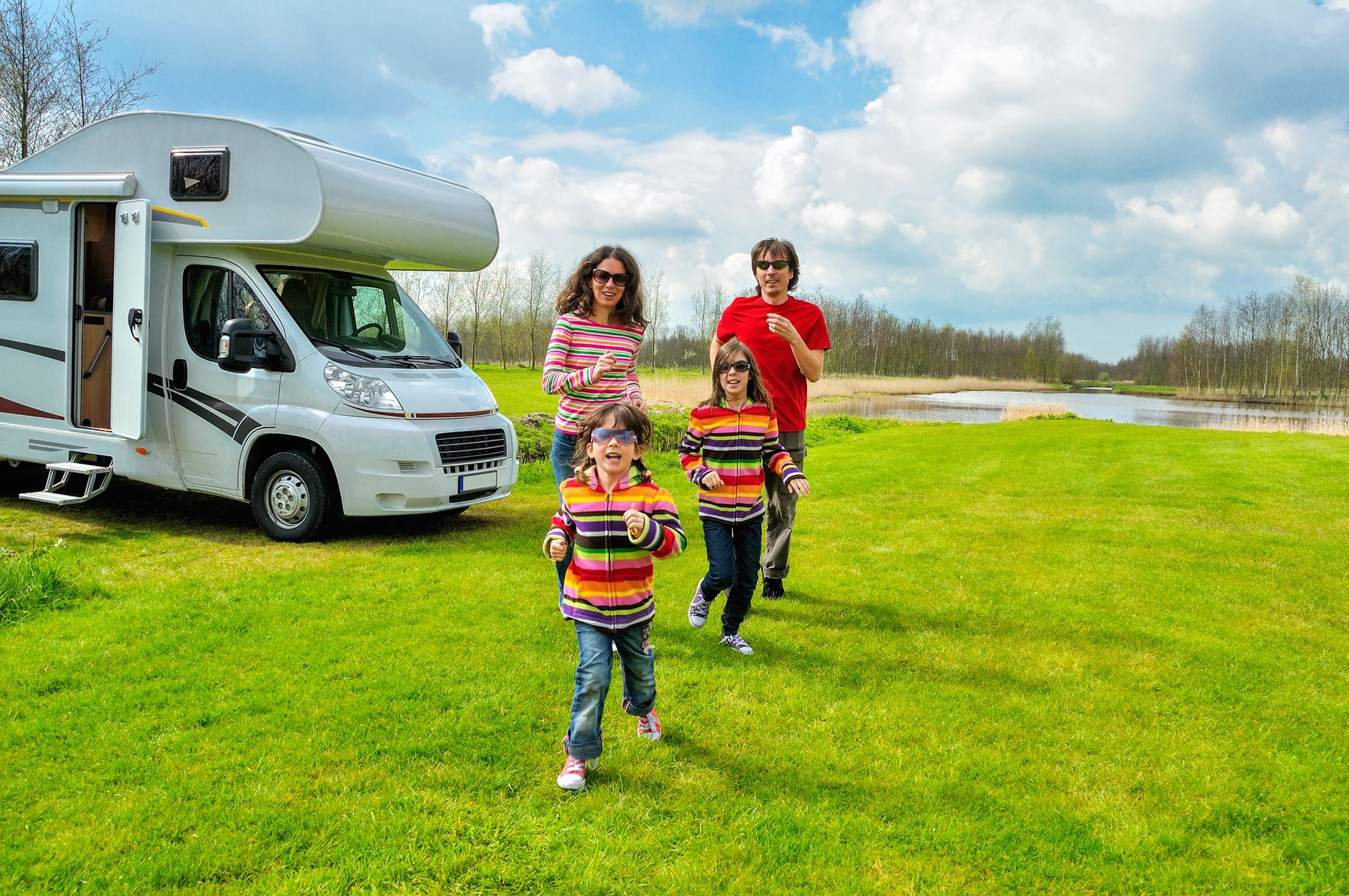 A family of four RV camping outdoors