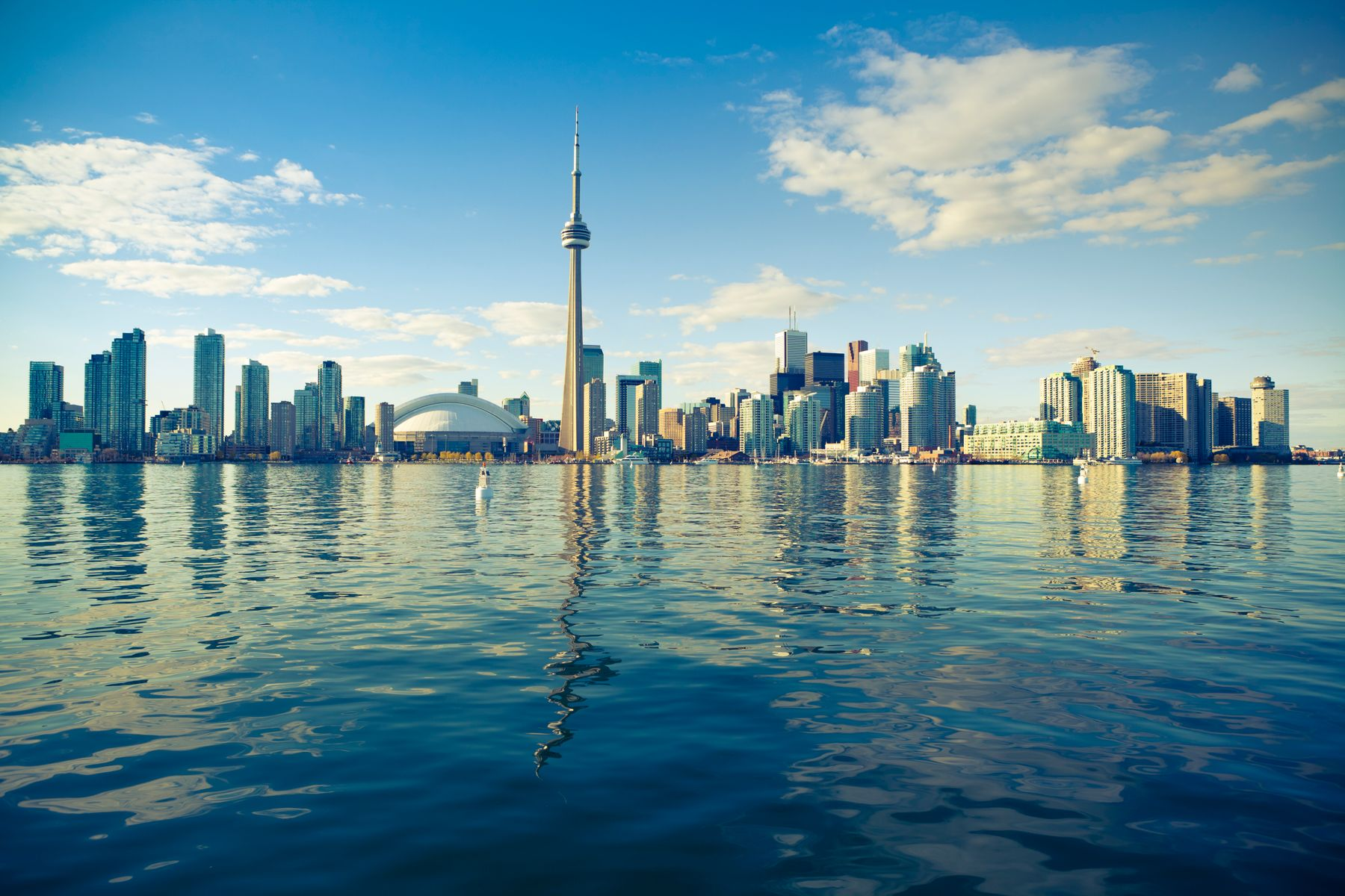 view of downtown toronto city skyline reflecting in lake ontario