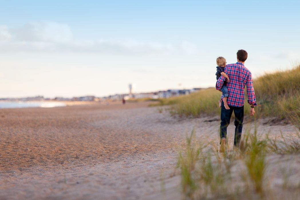 Πατέρας απολαμβάνει τη βόλτα του με το παιδί του στην παραλία - tips για φθηνές διακοπές με παιδιά