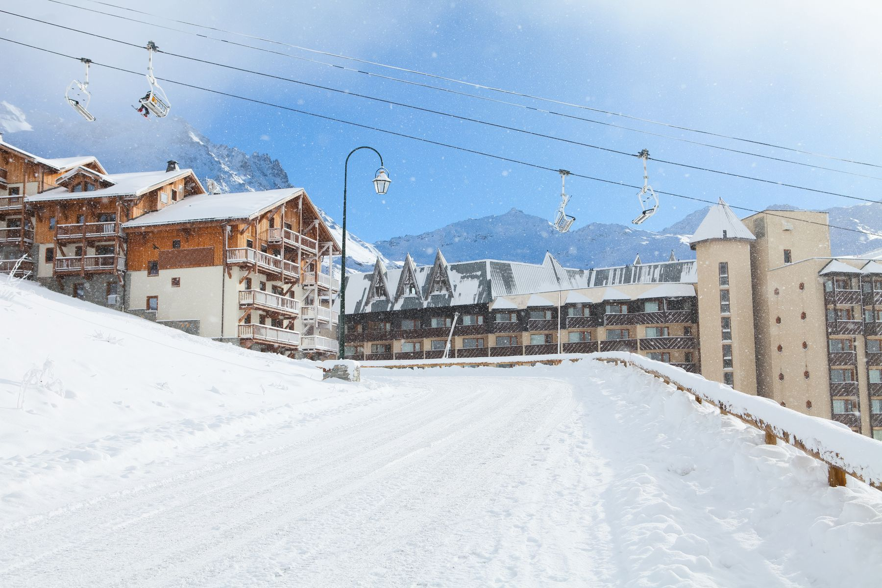 View of a chalet hotel with a ski lift running past it and a snowy road in the foreground