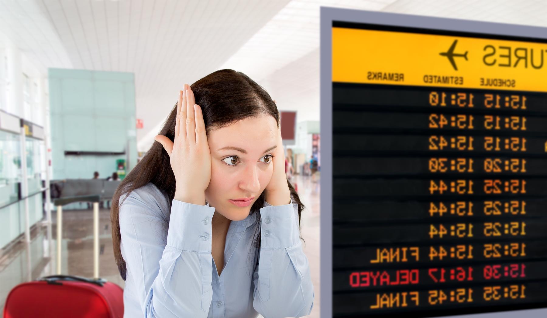 femme regardant l'écran des départs à l'aéroport