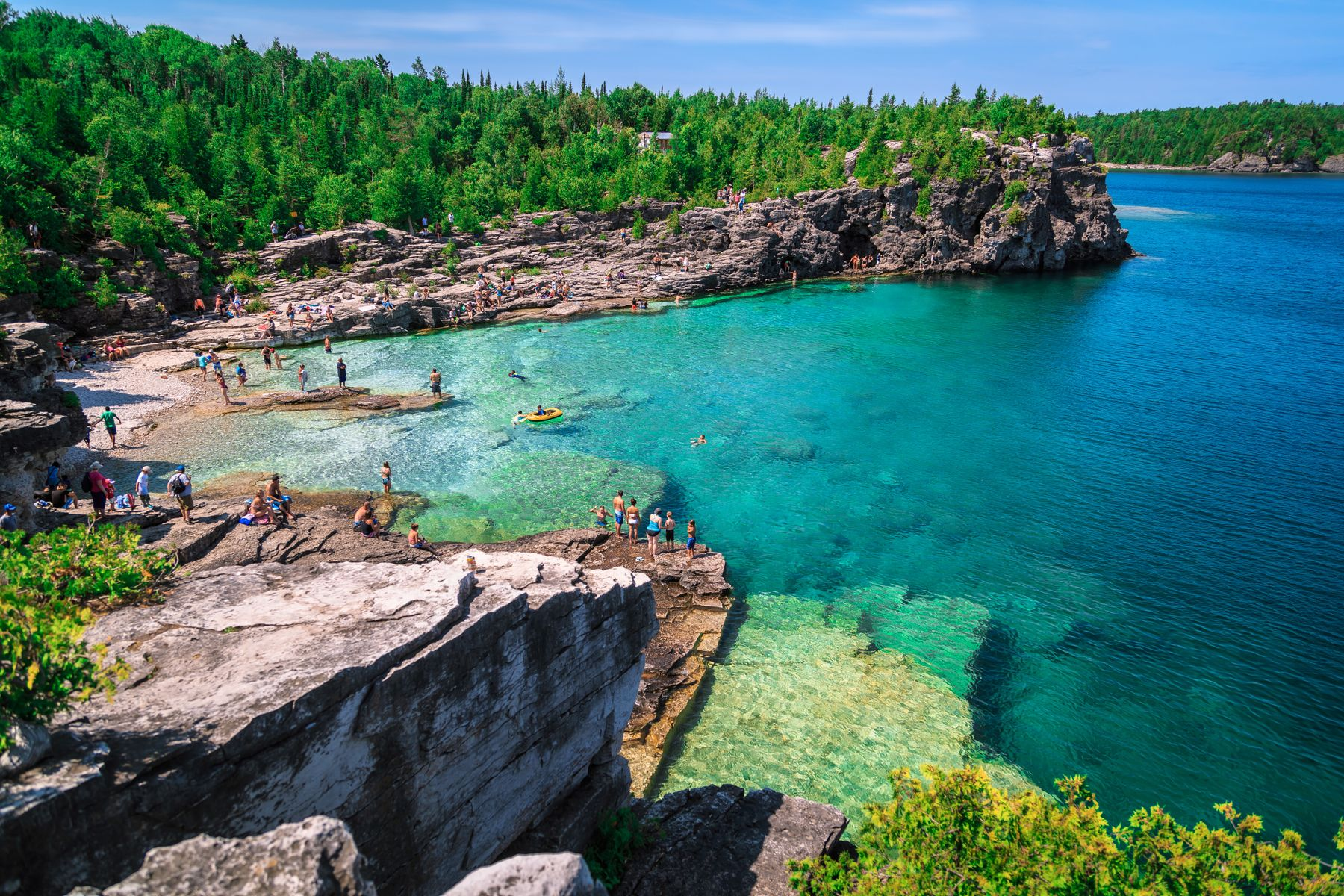 tourists standing along the rocky coastline of Flowerpot Island in Tobermory, a top tourist attraction in Ontario
