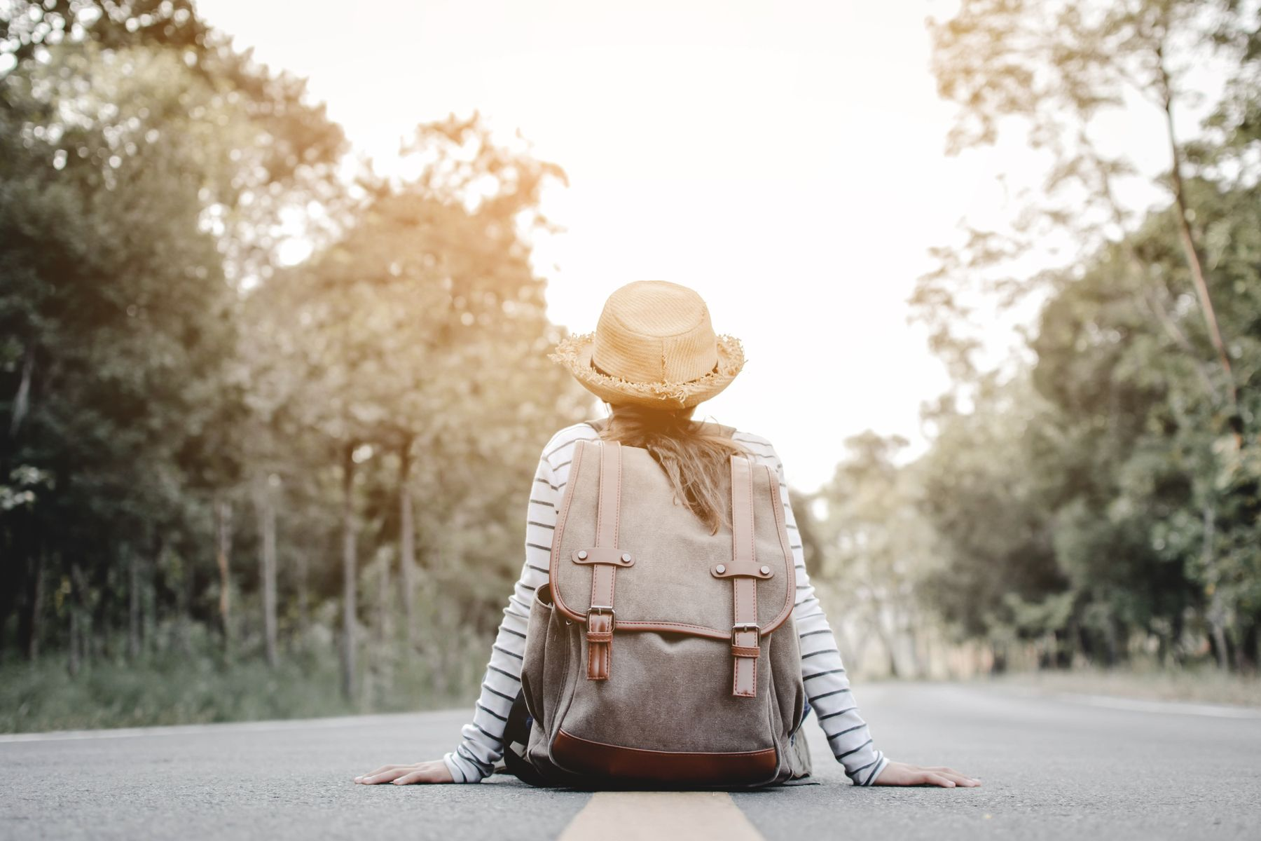 Alleinreisende Frau mit Rucksack sitzt auf der Straße.