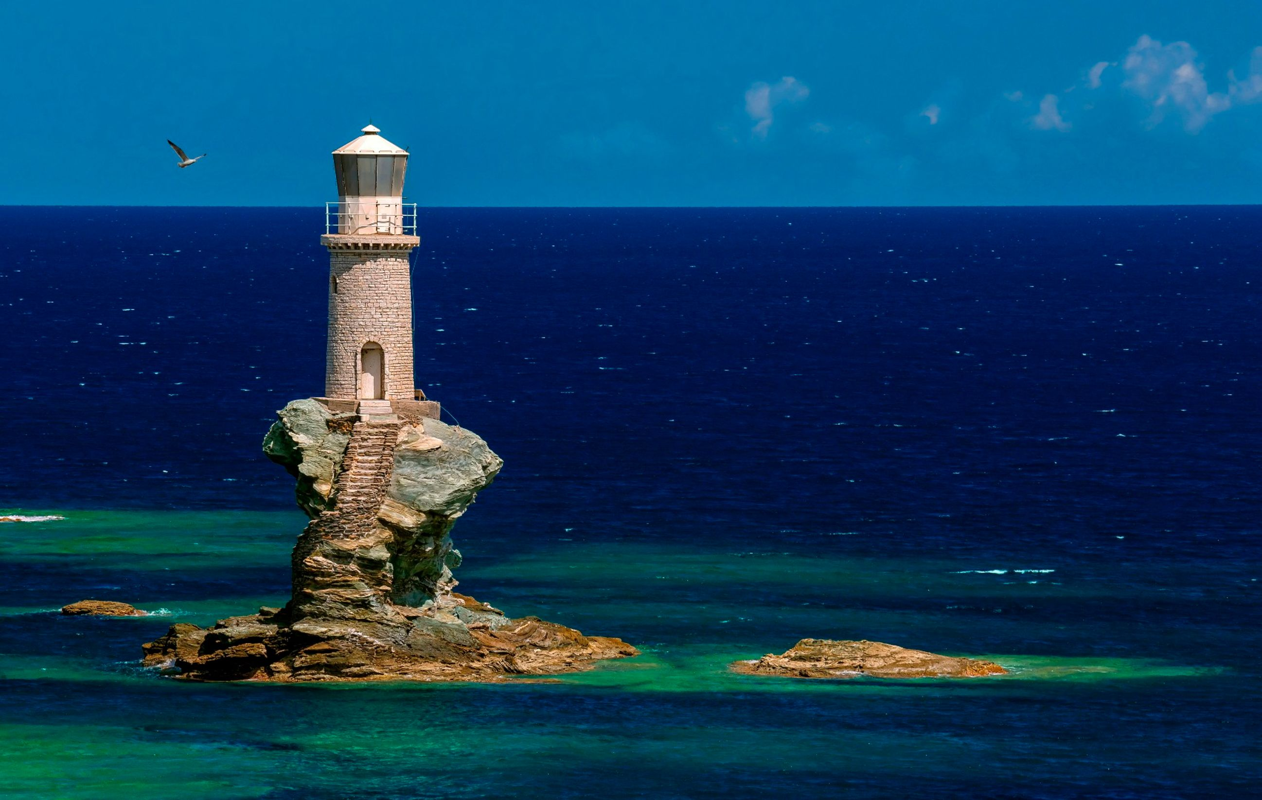 Faro Tourlitis - beautiful lighthouse perched on curved rock platform in Andros, Greece