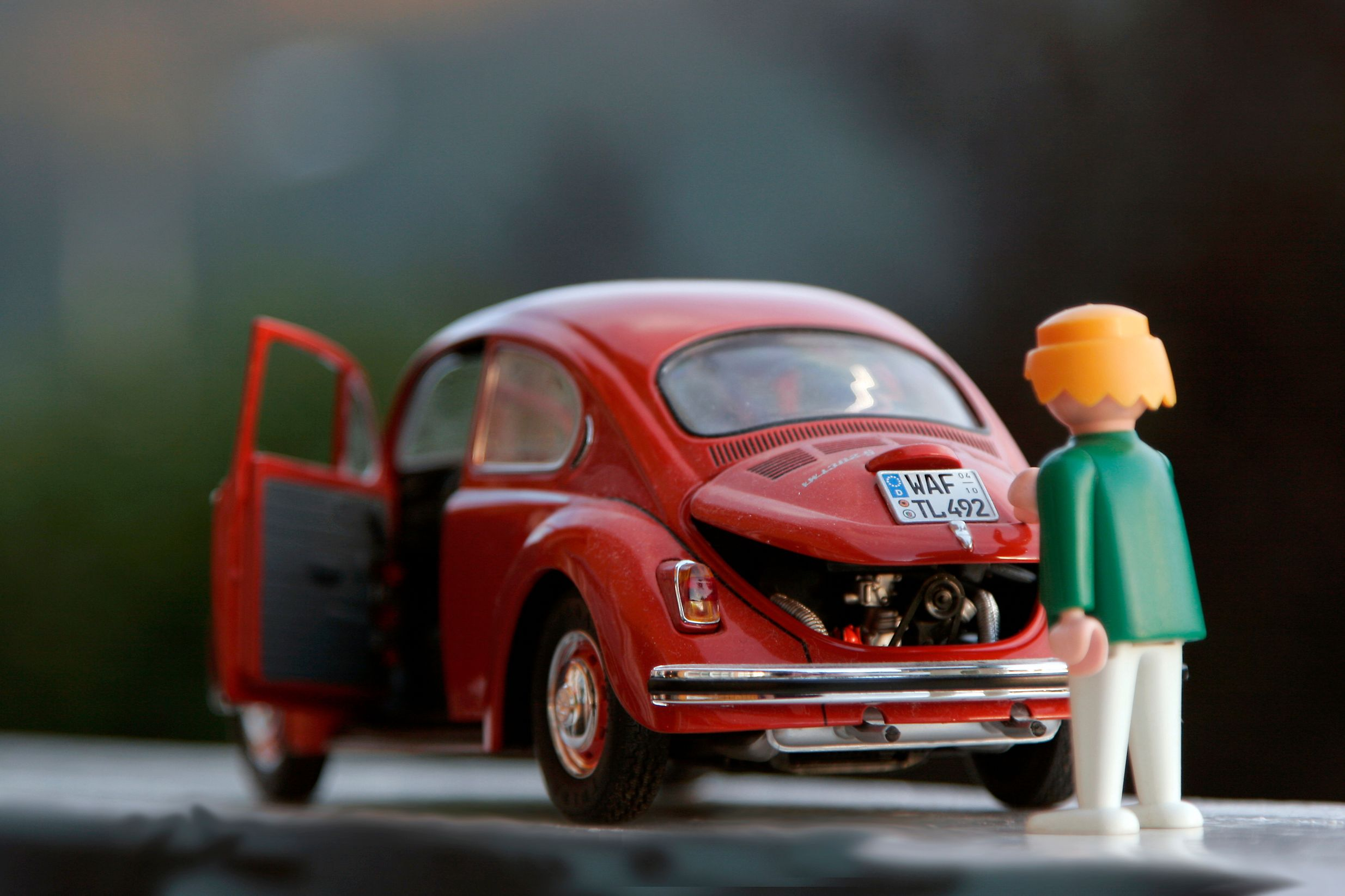 car figurine and toy closing toy car trunk before playing road trip games