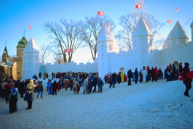 people outside of a snow sculpture castle in quebec city during a winter festival