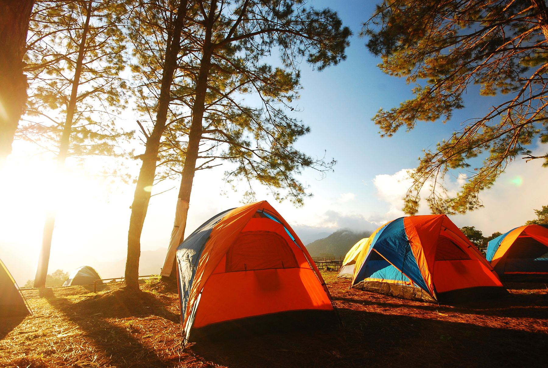 Row of colourful tents facing a sunrise