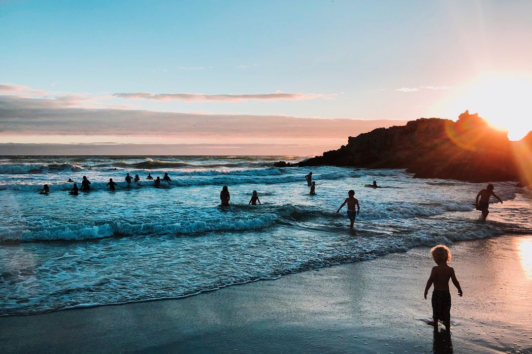 Παιδιά παίζουν στη θάλασσα το ηλιοβασίλεμα