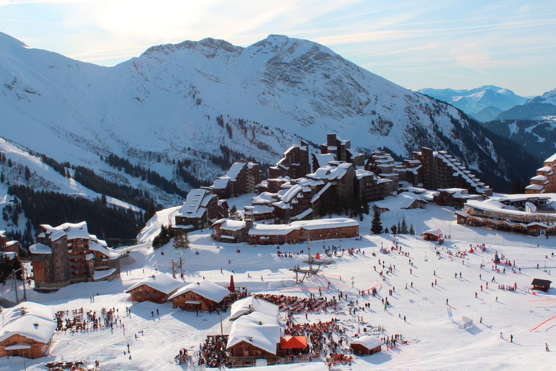 View of a busy but small ski resort from above, with a mountain in the background