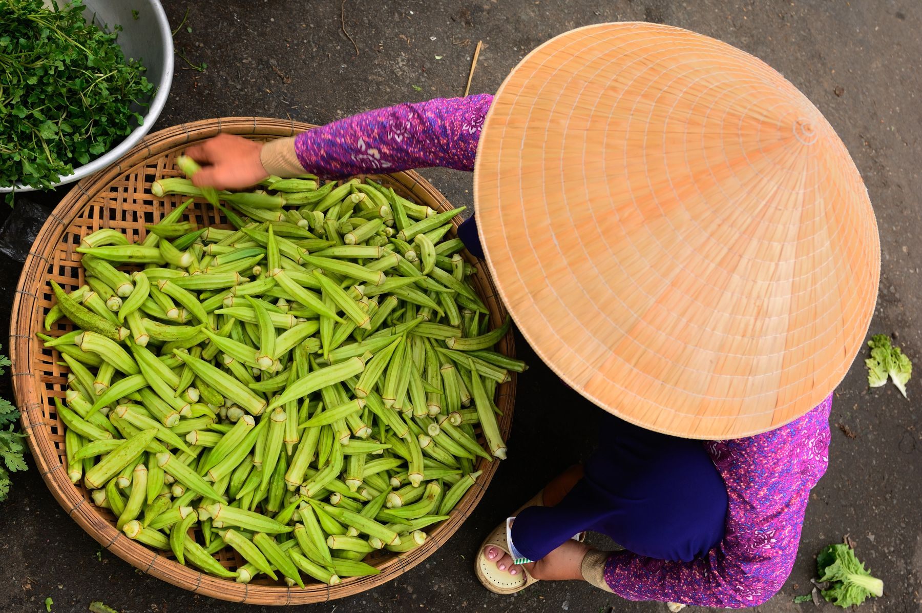 Vietnamese woman with bamboo hat selling veggies at a street market