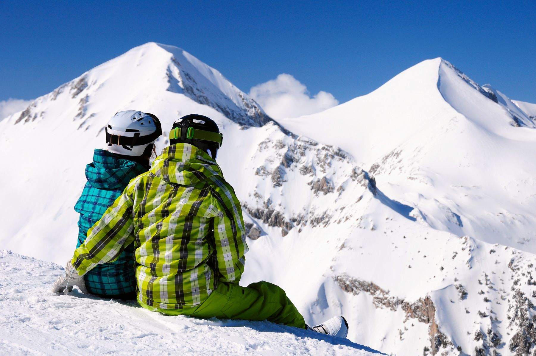 Two skiiers sit with their back to the camera looking at the mountains of Bansko, Bulgaria